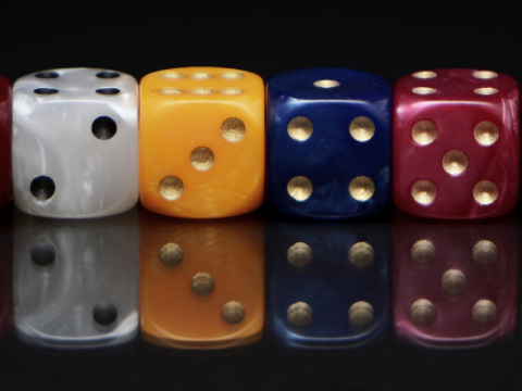 A picture of dice lined up in a row. They are all different colours, from left to right they